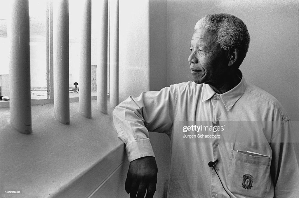 South Africa's first black President Nelson Mandela revisits his prison cell on Robben Island, where he spent eighteen of his twenty-seven years in prison, 1994.