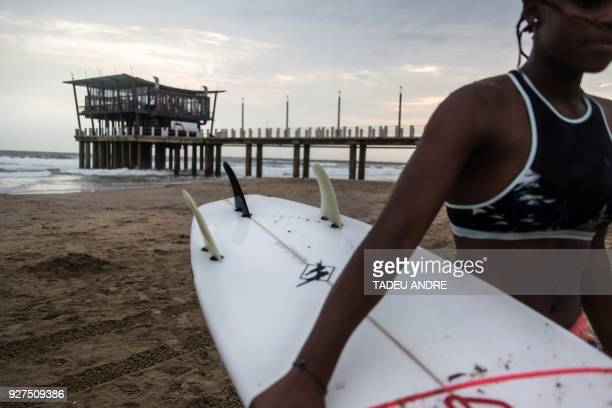 South Africa's first female Zulu professional surfer Samukeliswe Cele carries her surf board after an early morning practice session at Durban's...