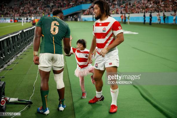 South Africa's flanker Siya Kolisi greets the daughter of Japan's hooker Shota Horie after the Japan 2019 Rugby World Cup quarterfinal match between...