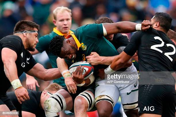 TOPSHOT South Africa's flanker Siya Kolisi is tackled by New Zealand's flyhalf Lima Sopoaga during the Rugby test match between South Africa and New...