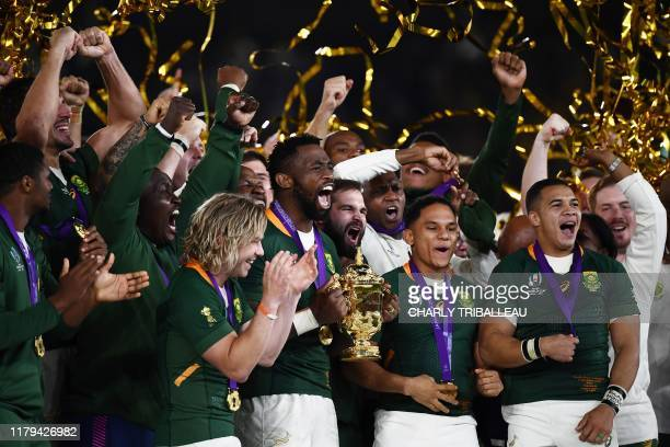 TOPSHOT South Africa's flanker Siya Kolisi lifts the Webb Ellis Cup as they celebrate winning the Japan 2019 Rugby World Cup final match between...