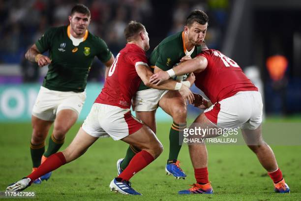 South Africa's flyhalf Handre Pollard is tackled by Wales' prop Dillon Lewis and Wales' flyhalf Dan Biggar during the Japan 2019 Rugby World Cup...