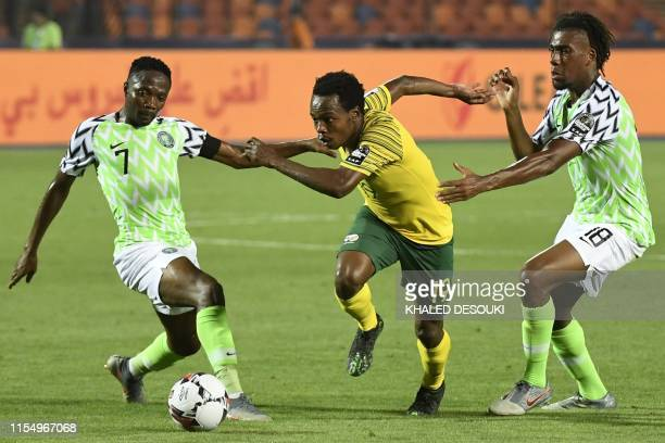 South Africa's forward Percy Tau dribbles past Nigeria's forward Ahmed Musa and Nigeria's forward Alex Iwobi during the 2019 Africa Cup of Nations...