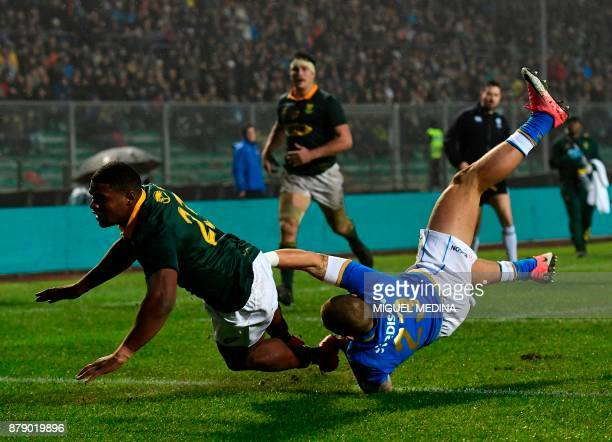 South Africa's fullback Warrick Gelant is tackled by Italy's fullback Matteo Minozzi during a rugby union test match between Italy and South Africa...