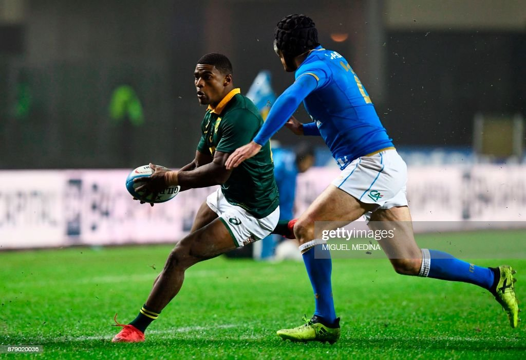 South Africa's fullback Warrick Gelant (L) runs to evade Italy's fly-half Ian McKinley during a rugby union test match between Italy and South Africa at the Euganeo Stadium in Padua on November 25, 2017. /