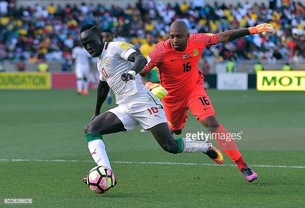 South Africa's goalkeeper Itumeleng Khune tries to prevent Senegal Sadio Mane from breaking through during the 2018 World Cup qualifying football...
