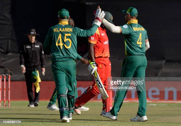 South Africa's Heinrich Klaasen and Aiden Markram celebrate after taking the wicket of Zimbabwe's Elton Chigumbura during the third One Day...
