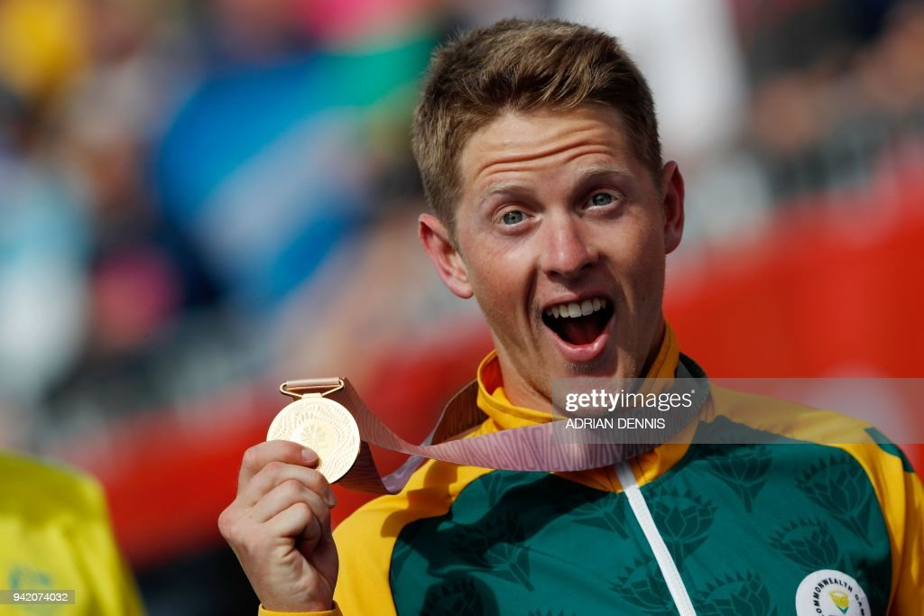 TOPSHOT - South Africa's Henri Schoeman holds his gold medal after winning the mens triathlon final during the 2018 Gold Coast Commonwealth Games at the Southport Broadwater Parklands venue in Gold Coast on April 5, 2018. /
