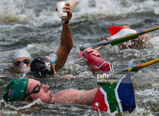 South Africa's Hercules Prinsloo grabs a drink during the men's 10km open water swimming marathon at the London 2012 Olympic Games at Hyde Park in...