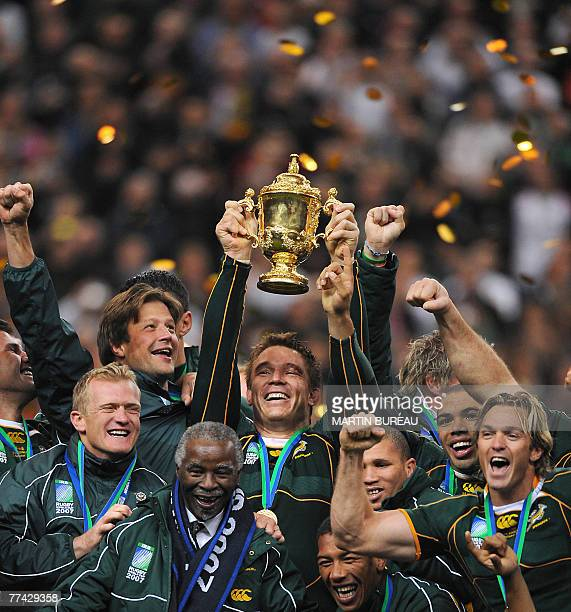 South Africa's hooker and captain John Smit holding the William Webb Ellis cup his teammates and South Africa president Thabo Mbeki celebrate after...