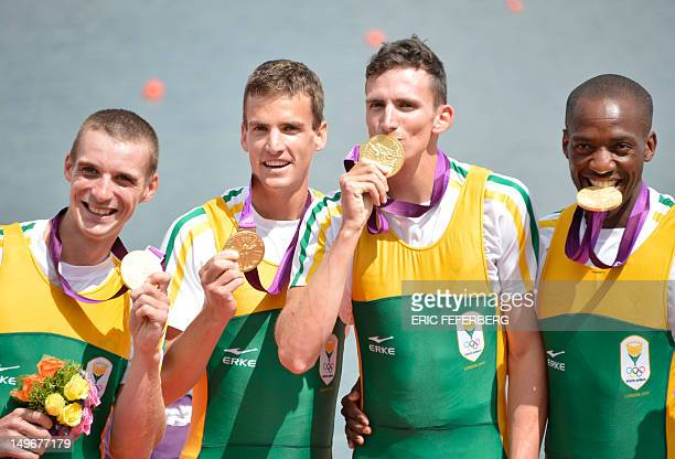South Africa's James Thompson Matthew Brittain John Smith and Sizwe Ndlovu pose on the podium after receiving the gold medal in the men's lightweight...