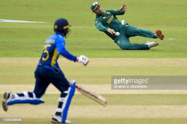 South Africa's Janneman Malan dives to stop a ball as Sri Lanka's Dhananjaya de Silva runs between the wickets during the first one-day international...
