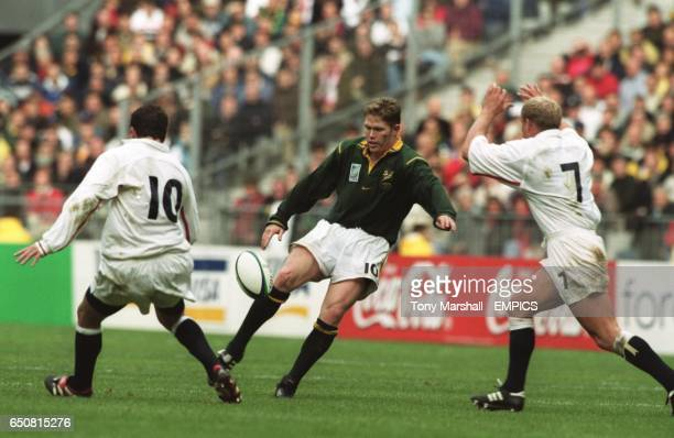 South Africa's Jannie De Beer chips the ball over England's Paul Grayson and Neil Back