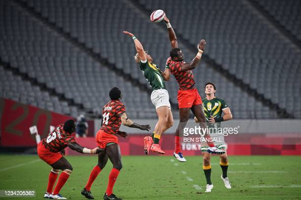 South Africa's JC Pretorius and Kenya's Willy Ambaka jump for the ball in the men's pool C rugby sevens match between South Africa and Kenya during...