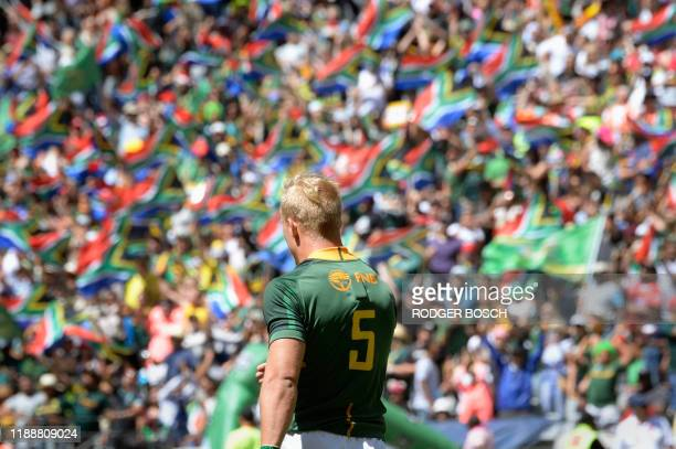 TOPSHOT South Africa's JC Pretorius walks after scoring a try while spectators wave South African national flags during the HSBC World Rugby Sevens...