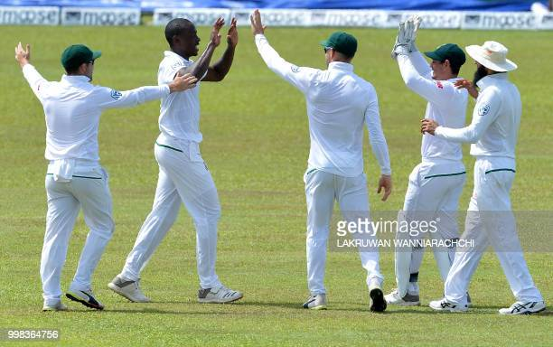 South Africa's Kagiso Rabada celebrates with his teammates after he dismissed Sri Lanka's Niroshan Dickwella during the third day of the opening Test...