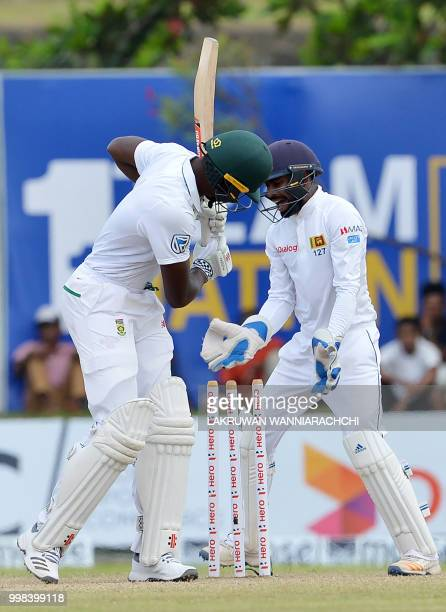 South Africa's Kagiso Rabada gets dismissed by Sri Lanka's Dilruwan Perera as wicketkeeper Niroshan Dickwella looks on during the third day of the...