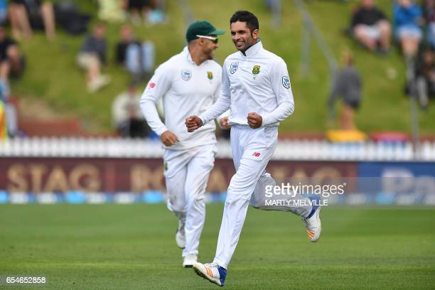South Africa's Keshav Maharaj and teammate captain Faf du Plessis celebrate New Zealand's Tim Southee being caught during day three of the second...