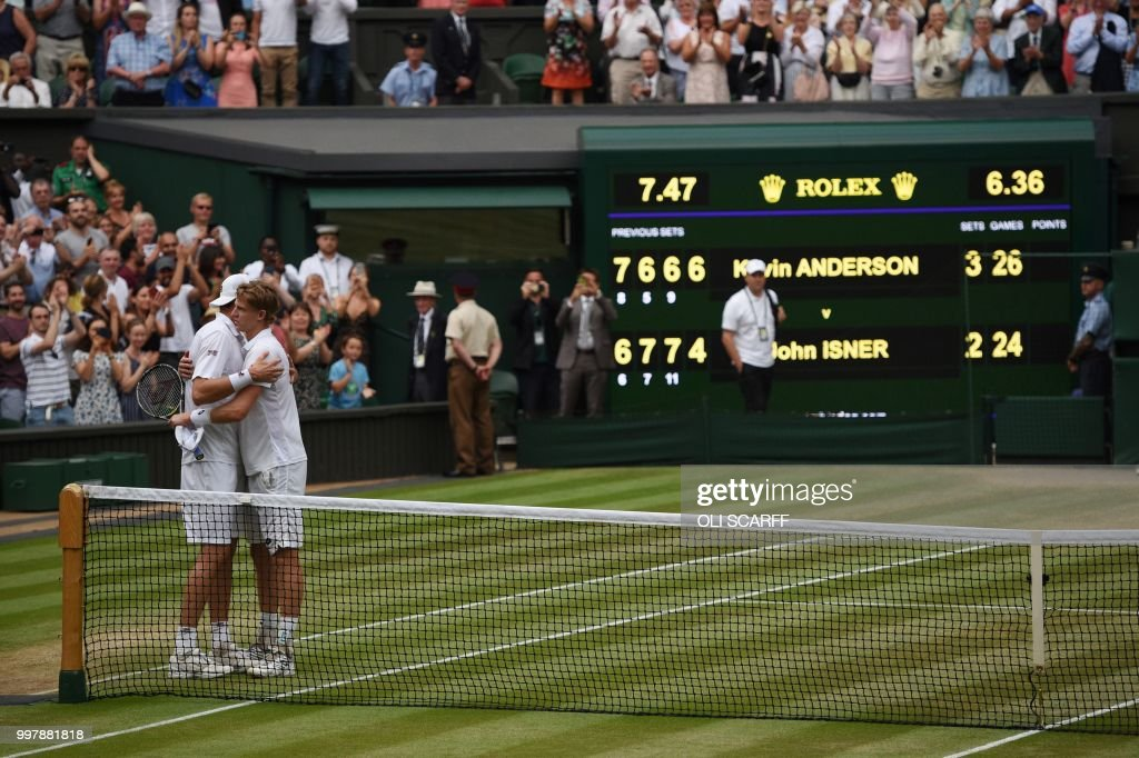 TOPSHOT - South Africa's Kevin Anderson (R) embraces US player John Isner after winning their men's singles semi-final match on the eleventh day of the 2018 Wimbledon Championships at The All England Lawn Tennis Club in Wimbledon, southwest London, on July 13, 2018. - Anderson won the match 7-6, 6-7, 6-7, 6-4, 26-24. (Photo by Oli SCARFF / AFP) / RESTRICTED