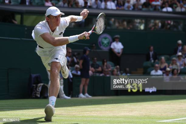 South Africa's Kevin Anderson returns against US player John Isner during their men's singles semifinal match on the eleventh day of the 2018...