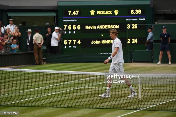 South Africa's Kevin Anderson walks past the score board after winning against US player John Isner during the final set tiebreak of their men's...