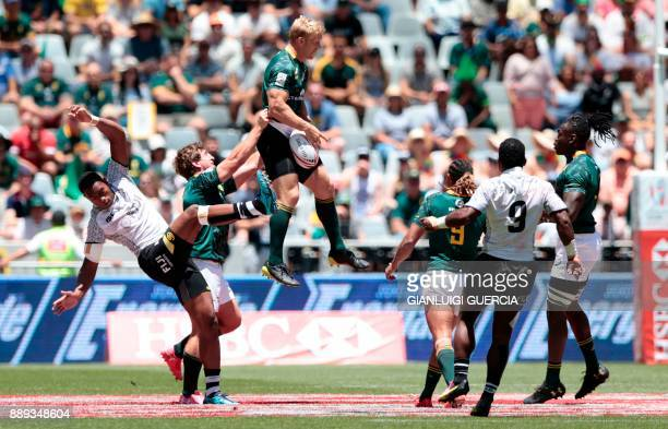 TOPSHOT South Africa's Kyle Brown jumps for the ball against Fijian players during their match on the second day of the World Rugby Sevens Series at...