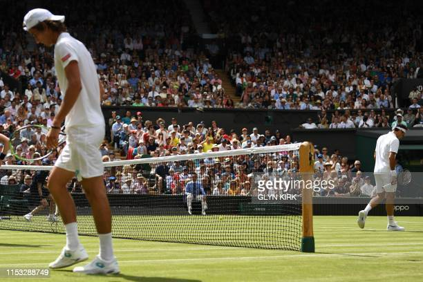 South Africa's Lloyd Harris and Switzerland's Roger Federer walk on the court during their men's singles first round match on the second day of the...