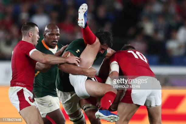 South Africa's lock Eben Etzebeth tackles Wales' full back Leigh Halfpenny during the Japan 2019 Rugby World Cup semifinal match between Wales and...