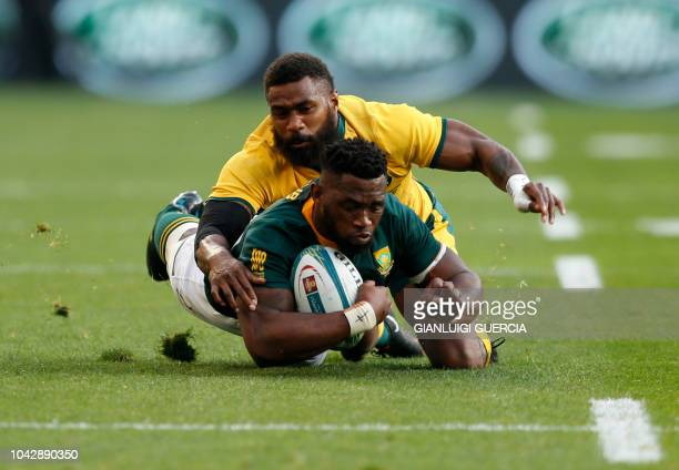 South Africa's loose forward Siya Kolisi is tackled by Australia's winger Marika Koroibete during the Rugby Championship match between South Africa...