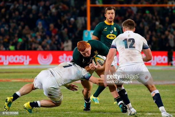 South Africa's loose head prop Steven Kitshoff is tackled by England prop Mako Vunipola during the second test match South Africa vs England at the...