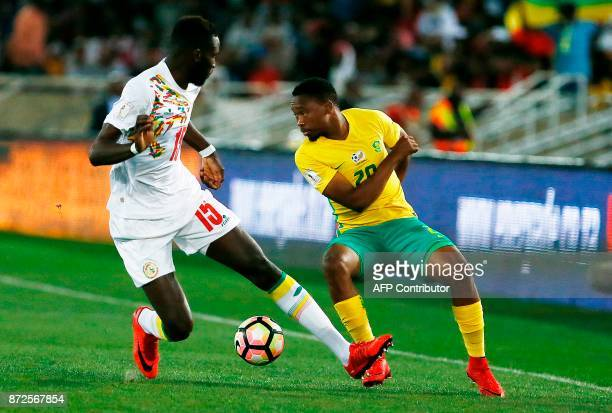 South Africa's midfielder Sibusiso Vilakazi vies for the ball with Senegal's midfielder Salif Sane during the FIFA World Cup 2018 qualification...