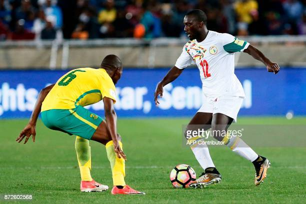 South Africa's midfielder Thamsanqa Mkhize vies for the ball with Senegal's defender Youssouf Sabaly during the FIFA 2018 World Cup Africa Group D...