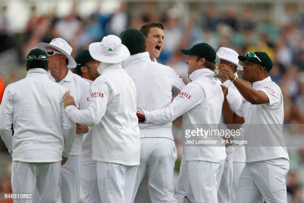 South Africa's Morne Morkel celebrates with the team after a TV review gives England's Andrew Strauss out LBW for 0 during the Investec first test...