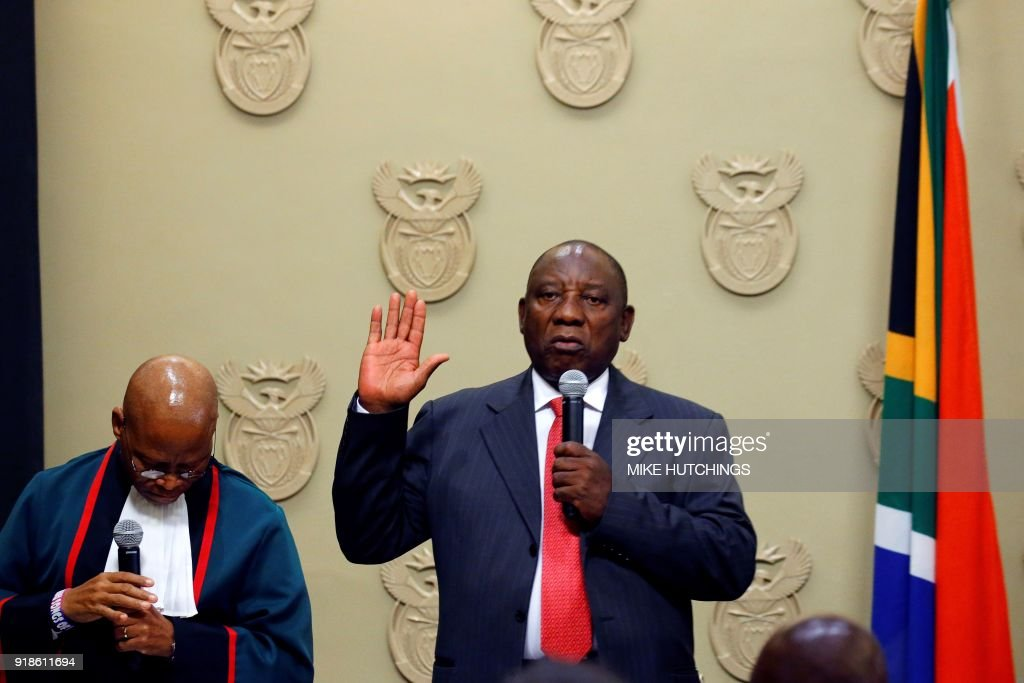 South Africa's new president Cyril Ramaphosa (R) holds up his right hand as he is sworn into office by South Africa's Chief Justice Mogoeng Mogoeng (L) after being elected by the Members of Parliament at the Parliament in Cape Town, on February 15, 2018. - South African lawmakers elected wealthy former businessman Cyril Ramaphosa on February 15, 2018 as the country's new president after scandal-tainted Jacob Zuma resigned under pressure from his own ANC ruling party. Ramaphosa was elected without a vote after being the only candidate nominated in the parliament in Cape Town, chief justice Mogoeng Mogoeng told assembled lawmakers.