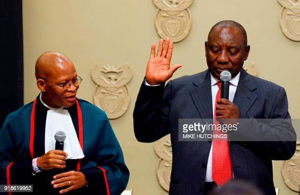 South Africa's new president Cyril Ramaphosa holds up his right hand as he is sworn into office by South Africa's Chief Justice Mogoeng Mogoeng after...