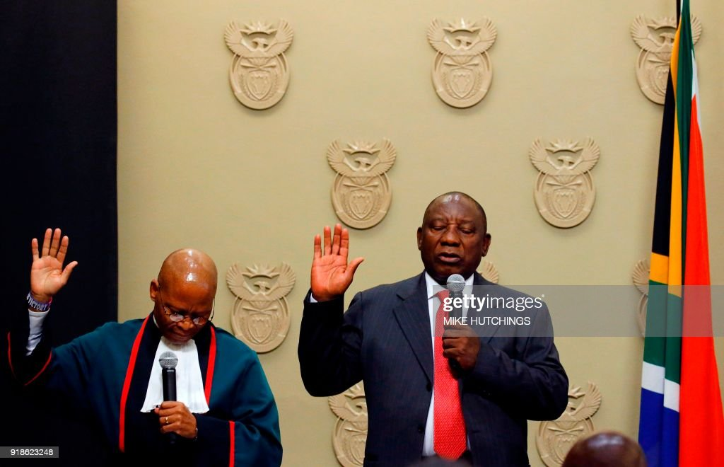 South Africa's new president Cyril Ramaphosa (R) holds up his right hand as he is sworn into office by South Africa's Chief Justice Mogoeng Mogoeng (L) after being elected by the Members of Parliament at the Parliament in Cape Town, on February 15, 2018. South African lawmakers elected wealthy former businessman Cyril Ramaphosa on February 15, 2018 as the country's new president after scandal-tainted Jacob Zuma resigned under pressure from his own ANC ruling party. Ramaphosa was elected without a vote after being the only candidate nominated in the parliament in Cape Town, chief justice Mogoeng Mogoeng told assembled lawmakers. HUTCHINGS