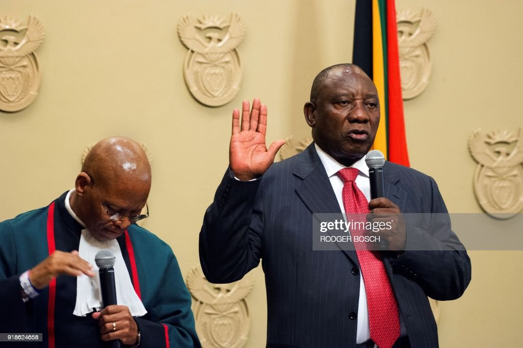 South Africa's new president Cyril Ramaphosa (R) holds up his right hand as he is sworn into office by South Africa's Chief Justice Mogoeng Mogoeng (L) after being elected by the Members of Parliament at the Parliament in Cape Town, on February 15, 2018. South African lawmakers elected wealthy former businessman Cyril Ramaphosa on February 15, 2018 as the country's new president after scandal-tainted Jacob Zuma resigned under pressure from his own ANC ruling party. Ramaphosa was elected without a vote after being the only candidate nominated in the parliament in Cape Town, chief justice Mogoeng Mogoeng told assembled lawmakers. PHOTO / POOL / Rodger BOSCH
