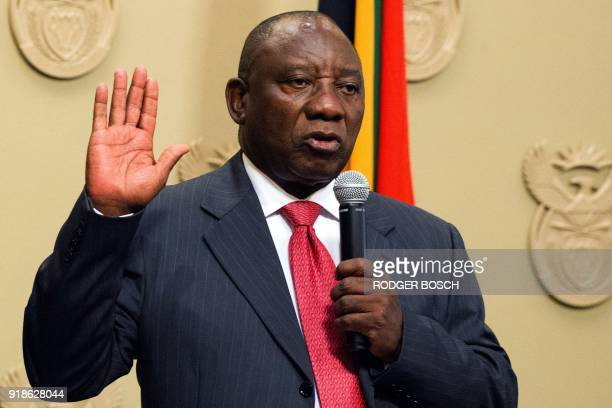 South Africa's new president Cyril Ramaphosa holds up his right hand as he is sworn into office after being elected by the Members of Parliament at...