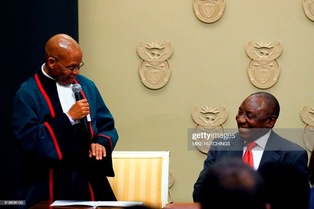 South Africa's new president Cyril Ramaphosa (R) reacts as he is sworn into office by South Africa's Chief Justice Mogoeng Mogoeng (L) after being elected by the Members of Parliament at the Parliament in Cape Town, on February 15, 2018. South African lawmakers elected wealthy former businessman Cyril Ramaphosa on February 15, 2018 as the country's new president after scandal-tainted Jacob Zuma resigned under pressure from his own ANC ruling party. Ramaphosa was elected without a vote after being the only candidate nominated in the parliament in Cape Town, chief justice Mogoeng Mogoeng told assembled lawmakers. HUTCHINGS