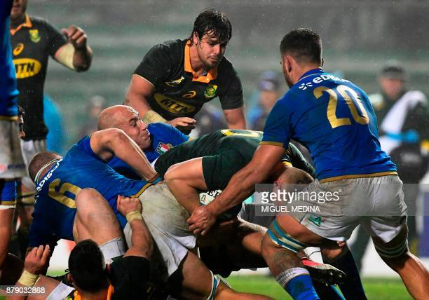 South Africa's number 8 Dan du Preez is tackled by Italy's flanker Giovanni Licata Italy's number 8 Sergio Parisse and Italy's flanker Renato...