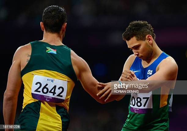 South Africa's Oscar Pistorius congratulates race winner Brazil's Alan Fonteles Cardoso Oliveira after the Men's 200 metres T44 athletics final...