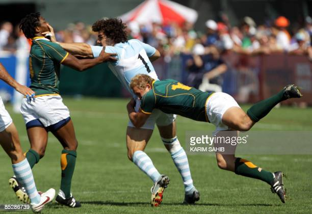 South Africa's Philip Snyman and Vuyo Zangqa try to block Argentina's Francisco Merello during their quarter final match on the third day of the...