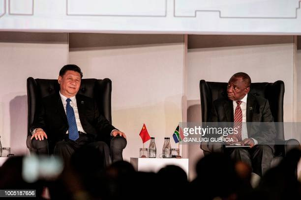 South Africa's President Cyril Ramaphosa looks at China's President Xi Jinping as they attend a Business Forum organised during the 10th BRICS summit...