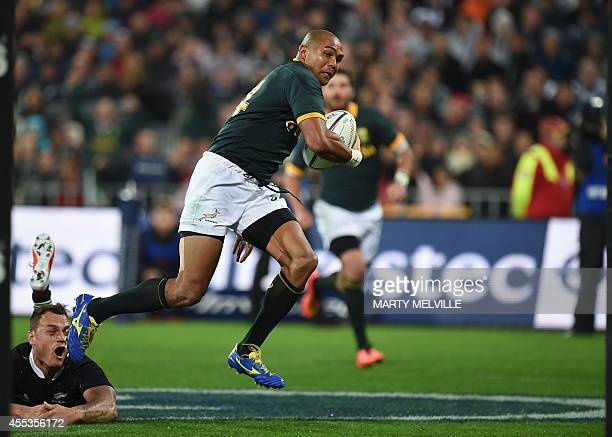 South Africa's right wing Cornal Hendricks runs out of a tackle by New Zealand's fullback Israel Dagg and runs in a try during the Rugby Championship...