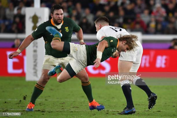 South Africa's scrumhalf Faf de Klerk attempts a tackle on England's centre Owen Farrell past South Africa's prop Frans Malherbe during the Japan...