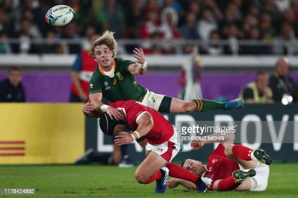 South Africa's scrumhalf Faf de Klerk is tackled by Wales' full back Leigh Halfpenny during the Japan 2019 Rugby World Cup semifinal match between...