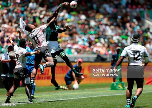 South Africa's Seabelo Senate jumps for the ball against Fijian defenders during their match on the second day of the World Rugby Sevens Series at...