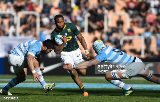 South Africa's Springboks Aphiwe Dyantyi is tackled by Argentina's Los Pumas Nahuel Tetaz Chaparro and Tomas Lavanini during the Rugby Championship...