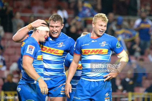 South Africa's Stormers no 8 Jaco Coetzee is congratulated by his teammates after scoring a try during the Super Rugby match between South Africa's...