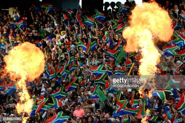 South Africa's supporters wave the national flag as they cheer for their team while fire flames raise from the pitch during the HSBC World Rugby...